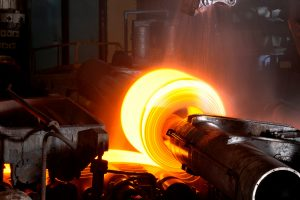 Steel manufacturing at industrial plant. hot steel coil is passed through rollers to compress in a thin steel sheet .